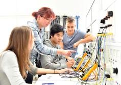 Lerhperson erklärt Lernenden technische Schalttafel