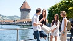 Gruppe Studierender an der Reuss mit Kappelbrücke im Hintergrund.