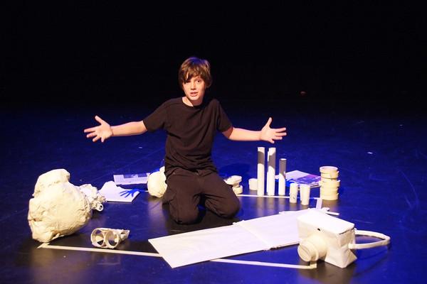 Kind mit Gegenständen auf Bühne.