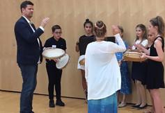 Schüler/-innen spielen unter Anleitung Tamburin.