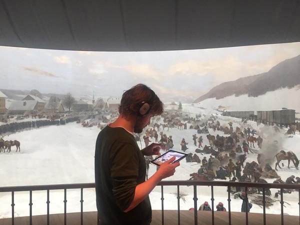 Junger Mann erarbeitet sich Informaten mit dem Tablett im Bourbaki-Panorama.